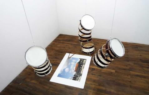 <p>(De gauche à droite) : Nicolas Fenouillat, <strong><em>Hélices</em></strong>, 2010, tom de batterie (12, 13, 16 pouces), peinture, tendeur élastique, <strong><em>Gradin (comment regarder un concert sur les toits)</em></strong>, 2010, impression jet d&rsquo;encre sur papier velvet, 841x1189mm, <strong><em>Mes premières baguettes</em></strong>, 2010, bronze. Vue de l&rsquo;exposition de Nicolas Fenouillat, Néon, Lyon, 2010. Photo : Maxime Rizard / Néon.</p>