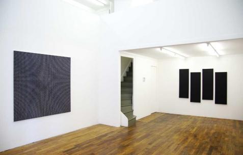 <p>De gauche à droite: Hugo Pernet, <strong><em>Mono 3</em></strong>, 2011, acrylique sur toile, 150x150cm. Hugo Schüwer-Boss, <strong><em>Black Flag 3D</em></strong>, 2011, acrylique sur toile, 4 toiles de 40x120cm. Vue de l&rsquo;exposition <em>Mute</em>, Néon, Lyon, 2011. Photo : JAC / Néon.</p>