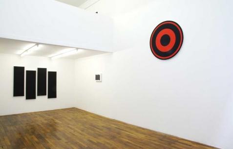 <p>De gauche à droite : Hugo Schüwer-Boss, <strong><em>Black Flag 3D</em></strong>, 2011, acrylique sur toile, 4 toiles de 40x120cm. Hugo Schüwer-Boss, <strong><em>Black Flag</em></strong>, 2007, acrylique sur toile, 30x40cm. Hugo Schüwer-Boss, <strong><em>Rise above</em></strong>, 2011, acrylique sur toile, 100 cm de diamètre. Vue de l&rsquo;exposition <em>Mute</em>, Néon, Lyon, 2011. Photo : JAC / Néon.</p>