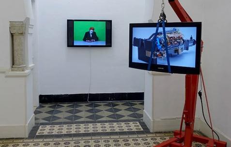 <p>(De gauche à droite) Selim Birsel, <strong><em>Craniopagus conjoined twin mushroom</em></strong>, 2006, vidéo, couleur, sonore, durée 4&rsquo;47. Mikaël Belmonte, <strong><em>Moteur V8</em></strong>, 2013, Grue d'atelier, écran plasma, sangles. Vue de l'exposition <em>Les Mondes Parallèles, </em>Galerie Nuage (Maison de France), Sfax, 2016. Photo: Georges Rey, 2016.</p>