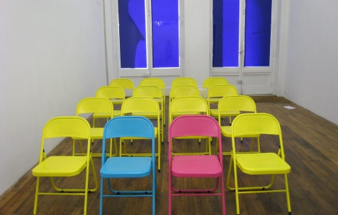 <p>Fanny Torres,<strong><em> Aristologie (dépeuplement)</em></strong> (détail), 2009, vidéo, karaoké, chaises et enceintes, dimensions variables. Vue de l'exposition <em>Aristologie</em>, Néon, Lyon 2009. Photo: Jean-Alain Corre.Photo: JRM.</p>