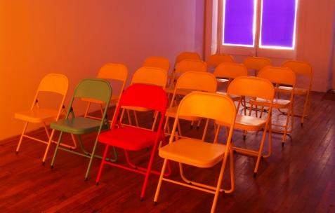 <p>Fanny Torres, <strong><em>Aristologie (dépeuplement)</em></strong> (détail), 2009, vidéo, karaoké, chaises et enceintes, dimensions variables. Vue de l'exposition <em>Aristologie</em>, Néon, Lyon 2009. Photo: Jean-Alain Corre.Photo: JRM.</p>